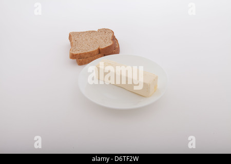 Butter stick on a white  table plate with two slices of wheat bread - Stock Photo