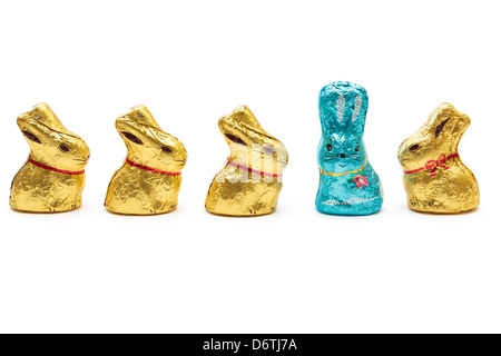 Four yellow gold wrapped chocolate Easter bunnies looking at one blue Easter bunny to illustrate stand out from - Stock Photo