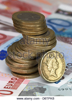 stack of one euro coins on top of euro notes with one pound coin leaning against them - Stock Photo