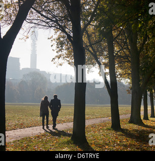 Couple walking through The Regent's Park in early autumn morning with BT Tower in silhouette in distance London - Stock Photo