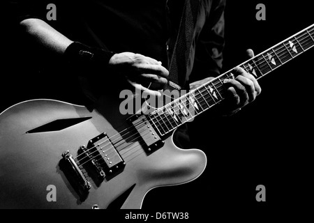 A guitarist tunes his guitar before playing in Melbourne, Australia - Stock Photo