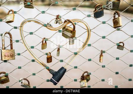 Locks including an heart shape lock on fence above river Yarkon in Israel - Stock Photo