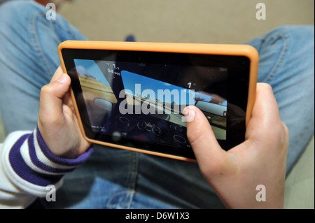 Twelve year old boy playing on a Kindle tablet. - Stock Photo