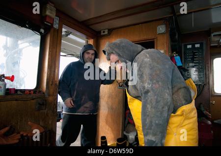 Fishermen dress for work. Stellwagen Banks, New England, United States, North Atlantic Ocean - Stock Photo