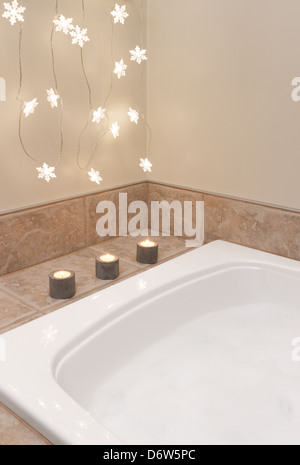 Bath with foam. Bathroom decorated with cozy lights and candles. - Stock Photo