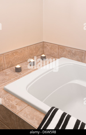 Bathroom with modern bathtub, decorated with candle lights. - Stock Photo
