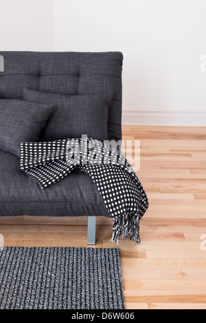 Gray sofa with cushions and throw. Living room detail. - Stock Photo