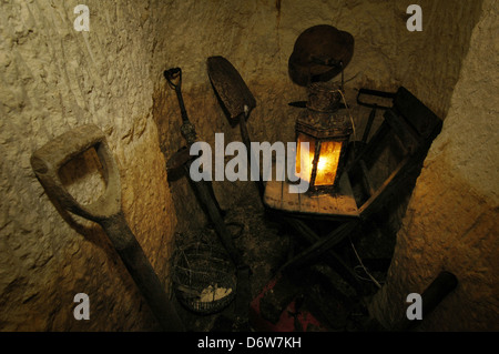 Digging tools displayed inside the 12 meter rock-hewn underground air-raid shelter used by locals during the WWII - Stock Photo