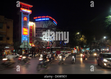 Horizontal nightscape of the exterior of the famous Thang Long water puppet theatre in Hanoi with traffic driving - Stock Photo
