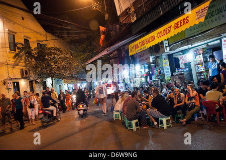 Horizontal wide angle of lots of tourists and locals drinking beer on the street in the Old Quarter in Hanoi at - Stock Photo