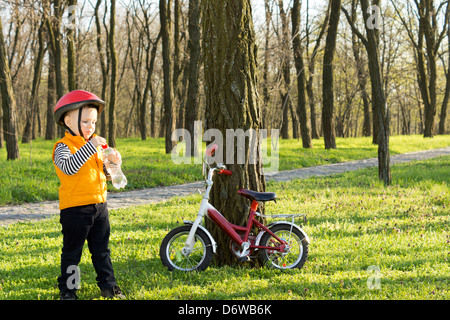 Little boy out riding his bicycle stopping amongst the trees in a wooded park for a drink of water from a plastic - Stock Photo