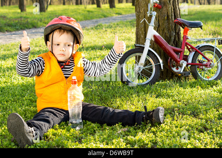 Small boy out riding his bicycle in the park giving a thumbs up of approval as he sits in his safety gear on green - Stock Photo