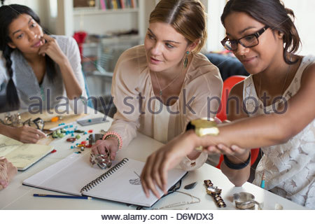 Female jewelry artists with sketch book and bracelets working at desk - Stock Photo