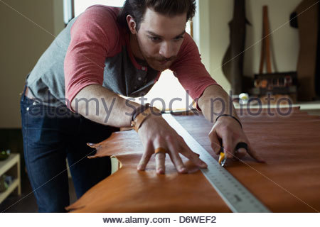 Young man measuring and cutting leather in workshop - Stock Photo