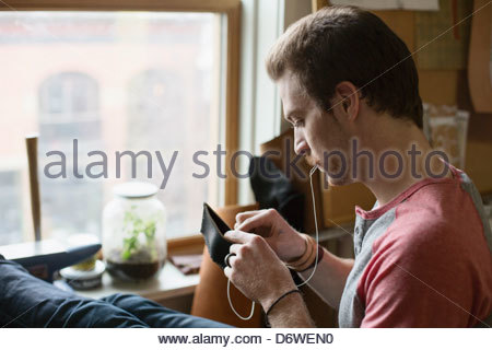 Young man sewing leather wallet in workshop - Stock Photo