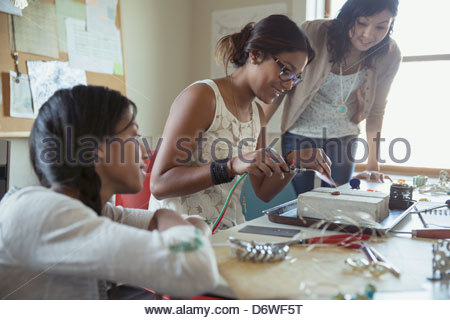 Female colleagues looking at woman using hand torch to make jewelry at workshop table - Stock Photo