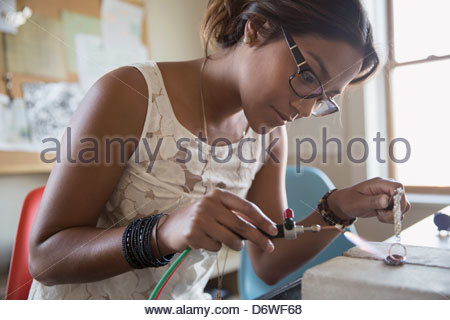 Young woman using hand torch to make jewelry - Stock Photo