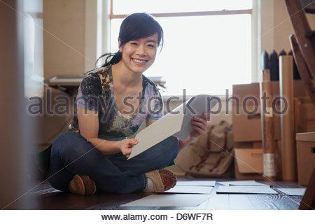 Portrait of happy female designer with prints sitting cross-legged on floor - Stock Photo