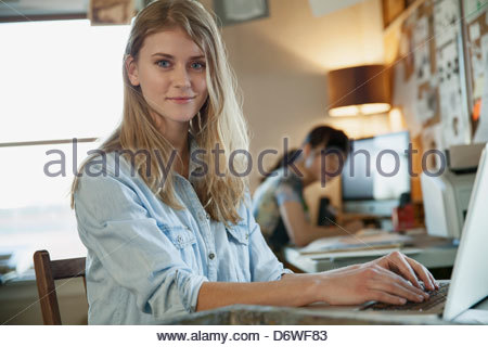 Portrait of beautiful woman working on laptop with colleague in background - Stock Photo