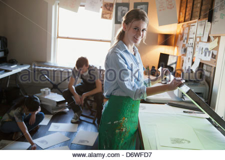Portrait of female printmaker with colleagues working in background - Stock Photo