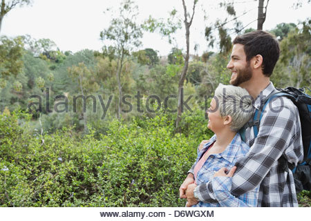 Side view of couple looking at view in forest - Stock Photo