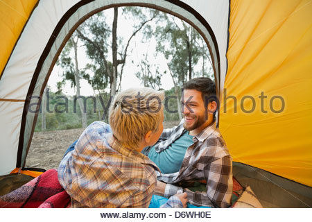 Couple relaxing in tent in forest - Stock Photo