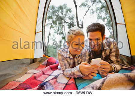 Happy couple using mobile phone together in tent - Stock Photo