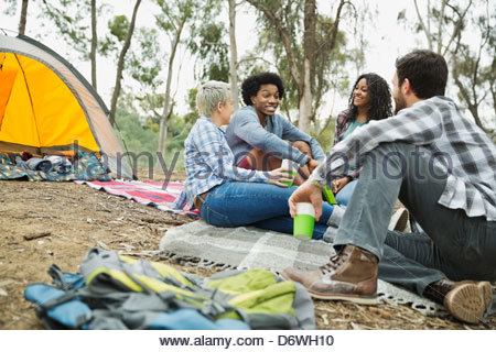 Friends talking while camping outdoors - Stock Photo