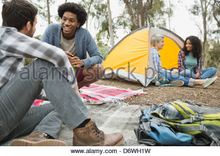 Happy friends talking while camping - Stock Photo