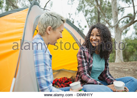 Happy female friends having a conversation while camping - Stock Photo