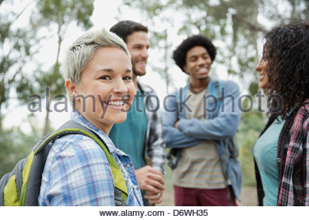 Portrait of happy mid adult woman with friends  in outdoors - Stock Photo