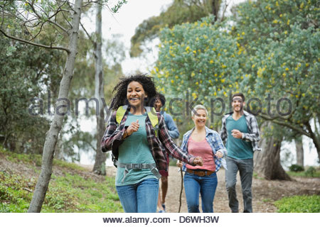 Happy friends running in forest - Stock Photo