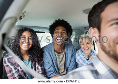 Portrait of happy teenage girl enjoying road trip with friends in truck - Stock Photo