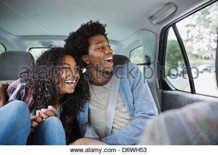 Cheerful couple looking through window while enjoying road trip - Stock Photo