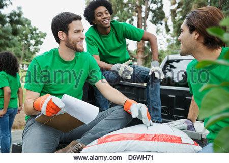 Happy male environmentalists having conversation on truck tailgate - Stock Photo
