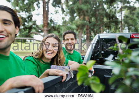 Happy environmentalists standing by pick-up truck in park - Stock Photo