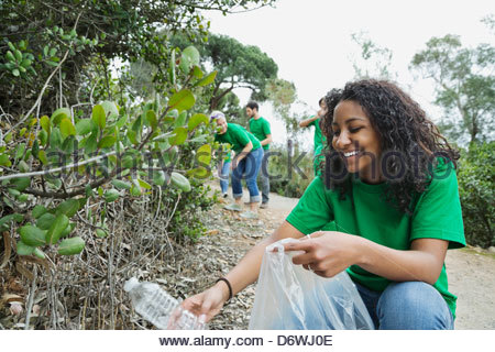 Happy teenage girl picking up empty water bottle with volunteers in background at park - Stock Photo
