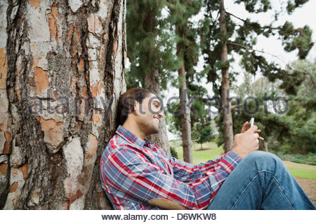 Side view of happy young man using mobile phone at park - Stock Photo