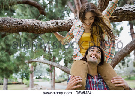 Happy young man carrying woman on shoulders in park - Stock Photo