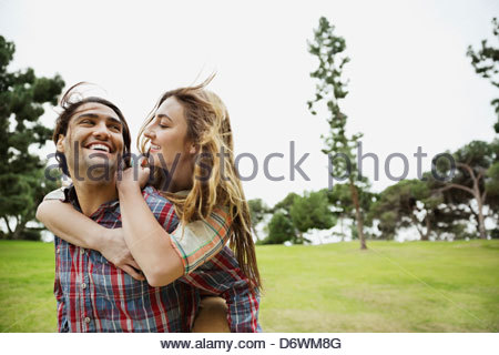 Happy man giving girlfriend a piggyback ride in park - Stock Photo