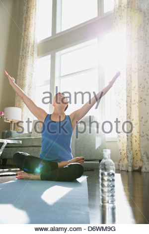 Mature woman with arms raised performing yoga against window at home - Stock Photo