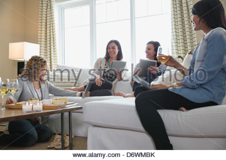 Mature female friends using digital tablets in living room - Stock Photo