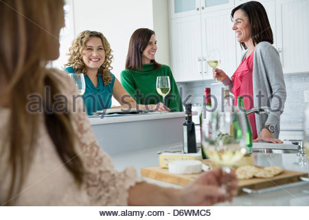 Happy female friends with wineglasses enjoying at house party - Stock Photo