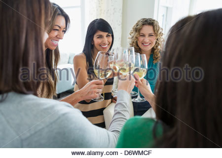 Happy female friends toasting wineglasses at house party - Stock Photo