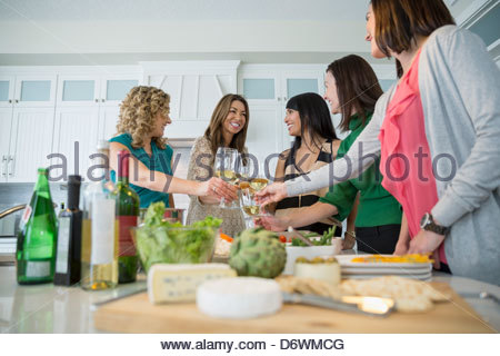 Happy female friends toasting wineglasses at kitchen island - Stock Photo