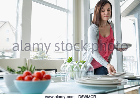 Mature woman arranging plates at dinner table - Stock Photo