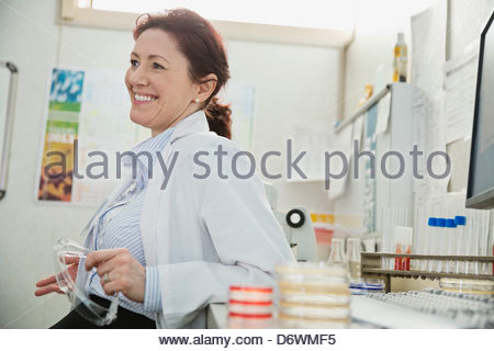 Happy female doctor looking away while leaning on desk in lab - Stock Photo