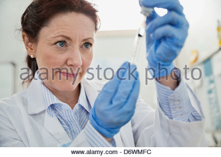 Mature female doctor filling syringe - Stock Photo
