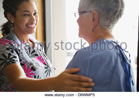 Young female doctor comforting patient in clinic - Stock Photo