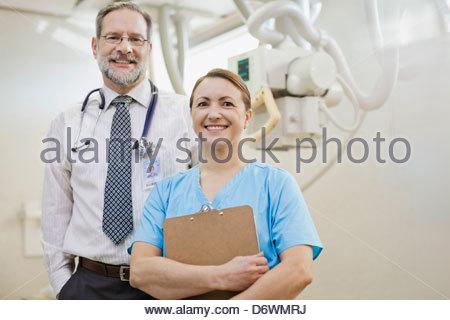 Portrait of confident mature doctors standing in examination room - Stock Photo